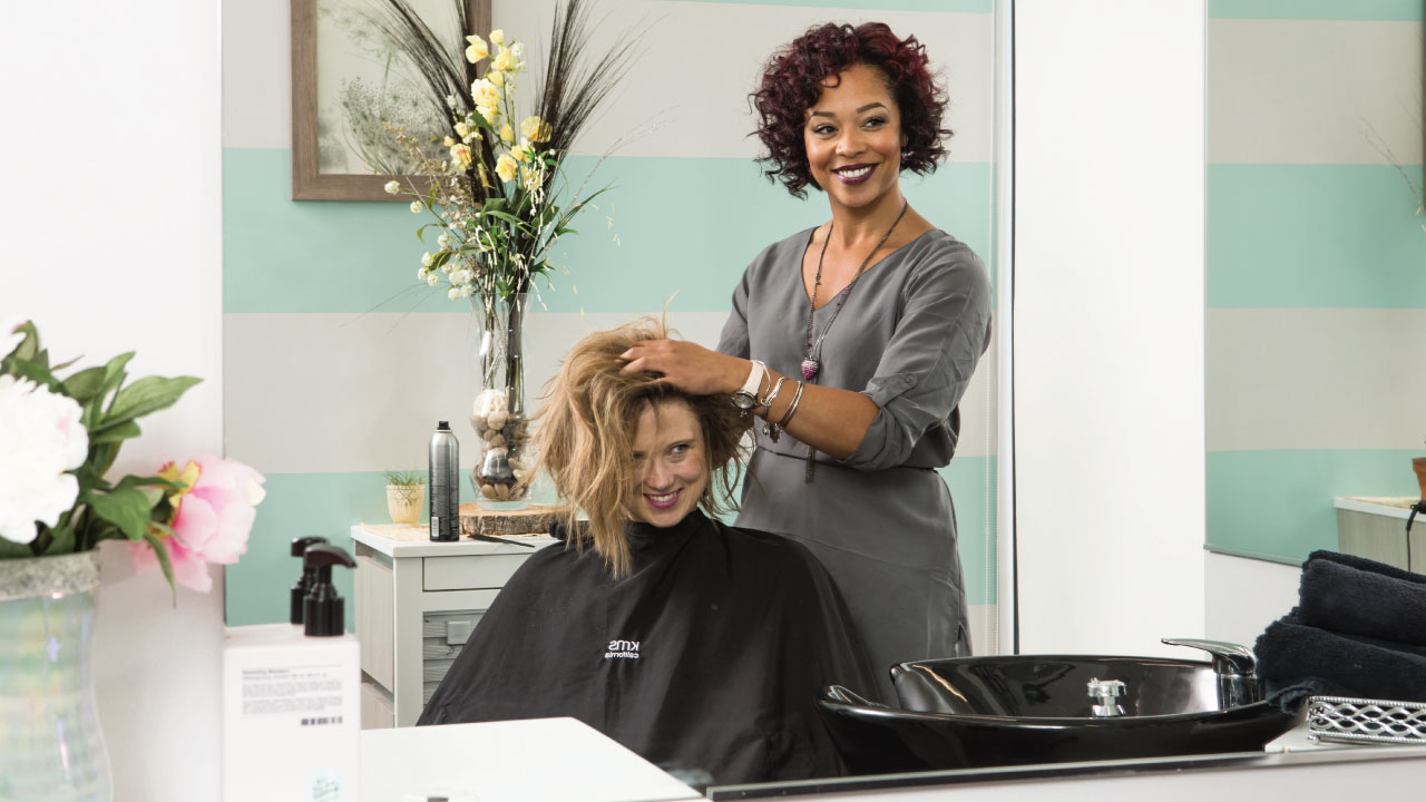 A smiling woman gets her hair styled by a proud salon professional